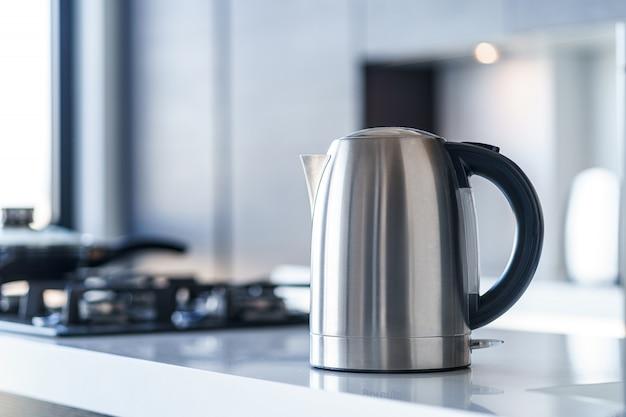 Silberner metall-wasserkocher zum kochen von wasser und zum zubereiten von tee auf einem tisch im kücheninneren. haushaltsküchengeräte für macht heiße getränke
