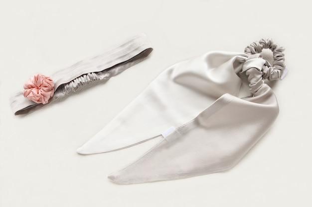 Silberner oder grauer haarschmuck mit textilrose. seidenhaargummi isoliert auf weißem hintergrund. flat lay friseurwerkzeuge und accessoires für damen - textilhaargummis, textilelastische haarbänder