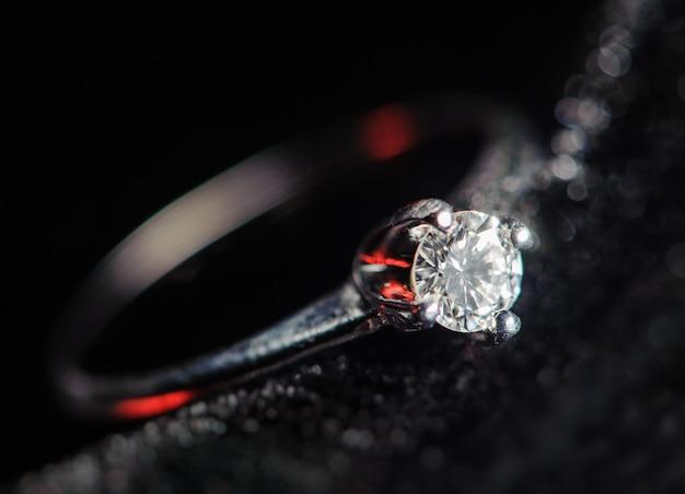 Silberner ring auf einem schwarzen hintergrund. makrobild