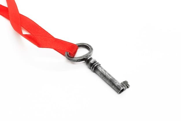 Silberner schlüssel der weinlese auf rotem band auf weißem hintergrund