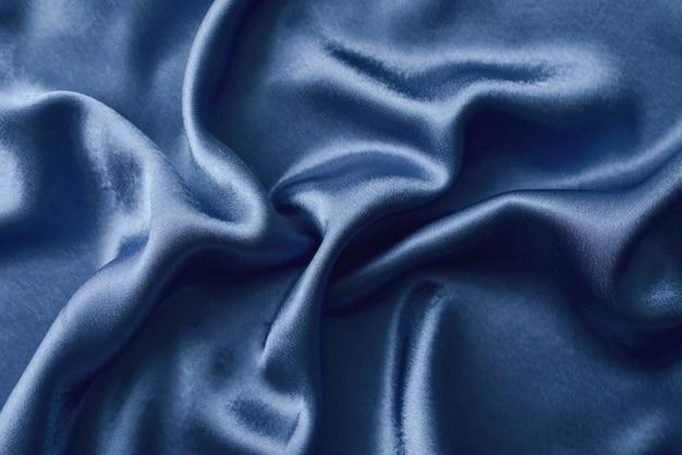 Silberner silk hintergrund mit falten. abstrakte beschaffenheit des geplätscherten silk hintergrundes