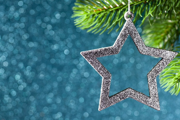 Silberner stern auf einem weihnachtsbaumzweig auf einem blau leuchtenden hintergrund von bokeh, nah oben.