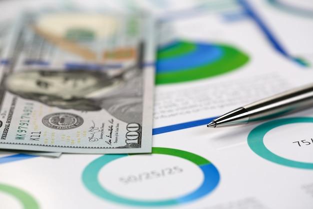 Silberner stift, der auf schreibtischbargeld-dollarplänen liegt