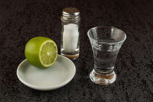 Silberner tequila mit kalk auf schwarzem hintergrund