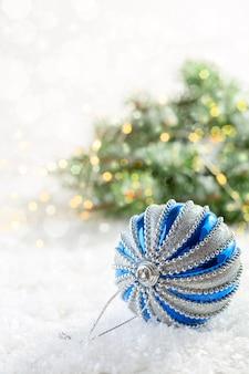 Silberner und blauer weihnachtsballon auf einem schneebedeckten tisch