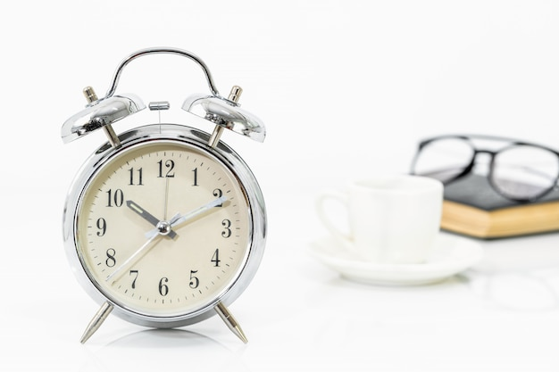 Silberner wecker, kaffeetasse, gläser und ein altes buch