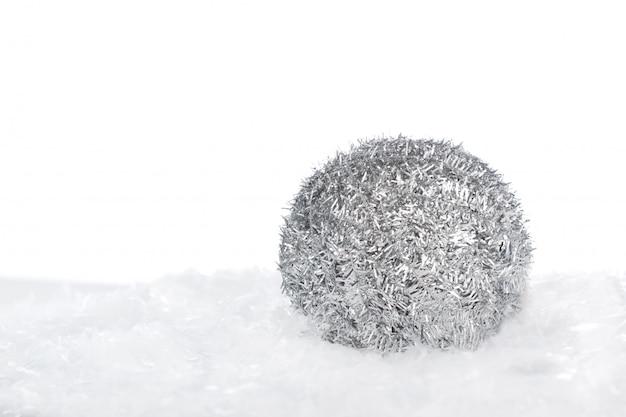 Silberner weihnachtsball auf dem schnee lokalisiert auf weißem hintergrund mit