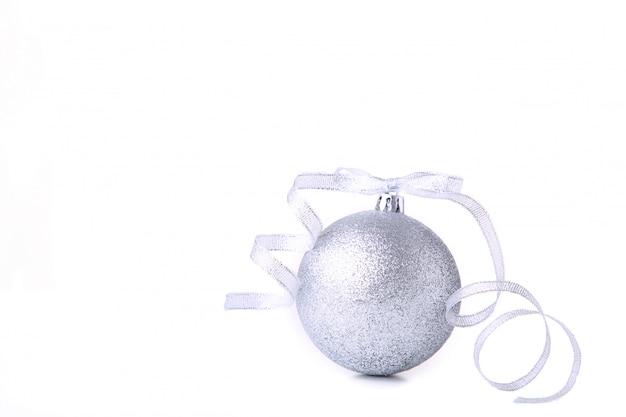 Silberner weihnachtsball mit band auf weißem hintergrund