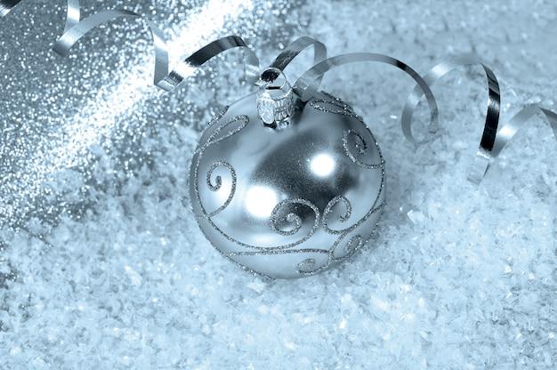Silberner weihnachtsflitter mit ausläufer und schnee