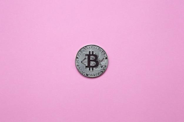 Silbernes bitcoin auf einem tausendjährigen rosa hintergrund. draufsicht minimalismus. horizontale ausrichtung flach legen