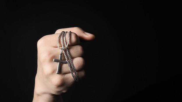 Silbernes kruzifix oder kreuzanhänger und halskette auf körper oder hand studioaufnahme schwarzer hintergrund