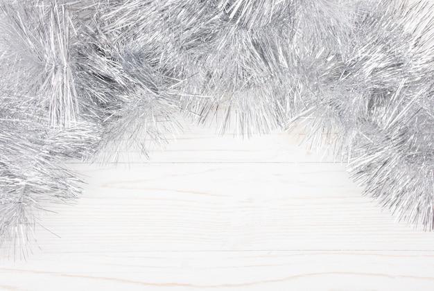 Silbernes lametta auf einem weißen hölzernen hintergrund