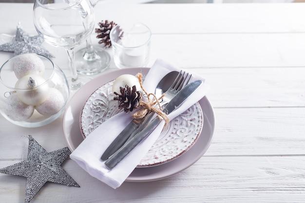 Silbernes und weißes weihnachtsgedeck mit weihnachtsdekorationen auf hölzernem hintergrund