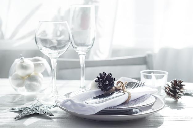 Silbernes und weißes weihnachtsgedeck mit weihnachtsdekorationen über hellem fenster