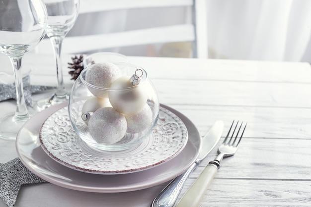 Silbernes und weißes weihnachtsgedeck mit weihnachtsdekorationen