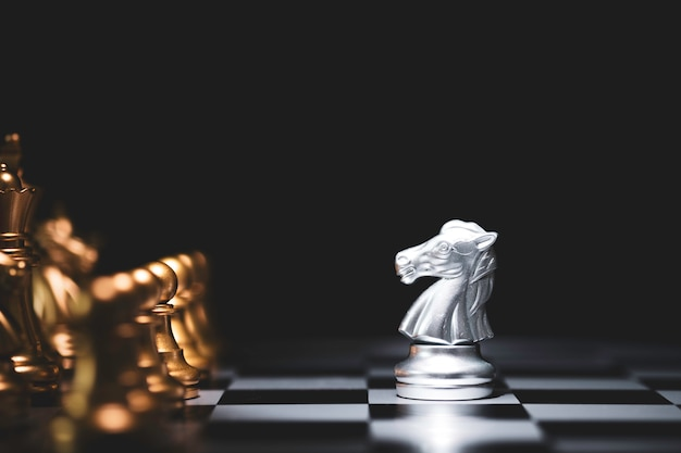 Silberpferdeschach trifft auf goldschachfeind auf schachbrett und schwarzem hintergrund.