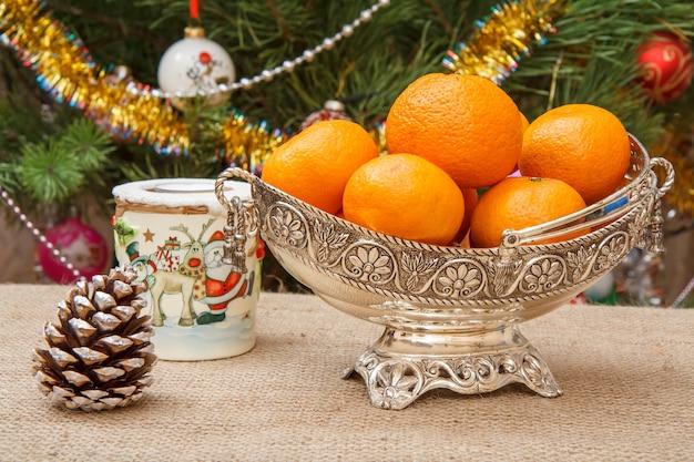 Silbervase mit orangen, kerze und kegel auf sackleinen. weihnachtsbaum mit spielzeugbällen und girlanden im hintergrund. heiligabend-konzept.