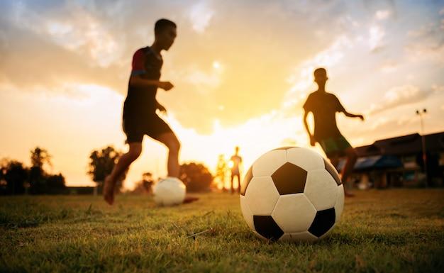 Silhouete-aktionssport draußen einer gruppe kinder, die den spaß spielt fußballfußball haben