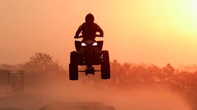 Silhouette atv oder quad bikes springen sie in den sonnenuntergang