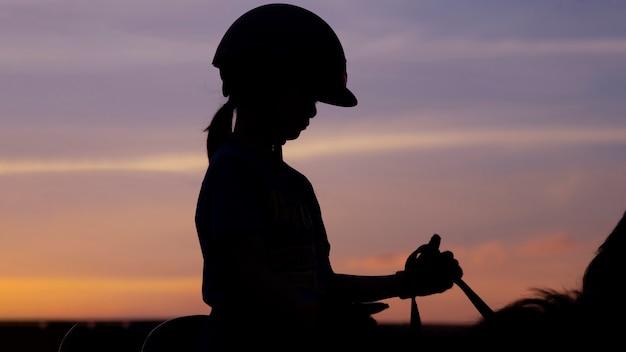 Silhouette bild des reitpferdes des schulkindmädchens gegen den zwielichthimmel.