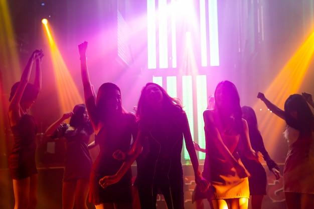 Silhouette bild von menschen tanzen in disco nachtclub zu musik von dj auf der bühne