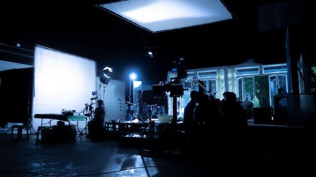 Silhouette bilder der videoproduktion hinter den kulissen oder b-roll oder making-of-tv-werbefilme, die filmteam team lightman und video-kameramann mit filmregisseur im studio zusammenarbeiten.