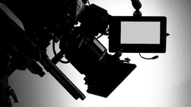 Silhouette bilder von videokameras in der kommerziellen tv-studio-produktion, die von kameramann und filmteam in set und requisite auf professionellen kran und stativ für einfache bedienung betrieben oder gedreht werden