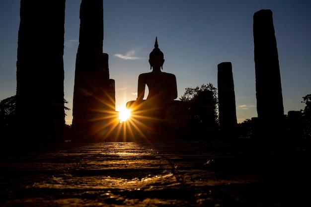 Silhouette buddha bild burst sun sukhothai wat mahathat buddha statuen thailand.
