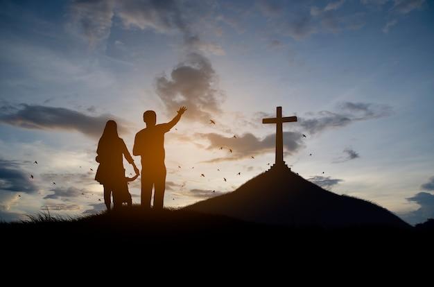 Silhouette christliche familie, die mit kreuz für anbetungsgott steht
