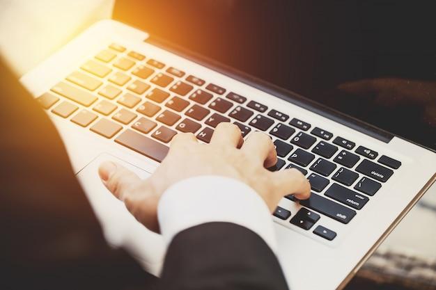 Silhouette der abgeschnittenen schuss von einem jungen geschäftsmann arbeitet auf notebook-computer an seinem arbeitsplatz mit technologie, flare licht.