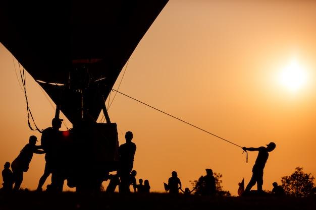 Silhouette der arbeiter ziehen heißluftballon korb im sonnenuntergang