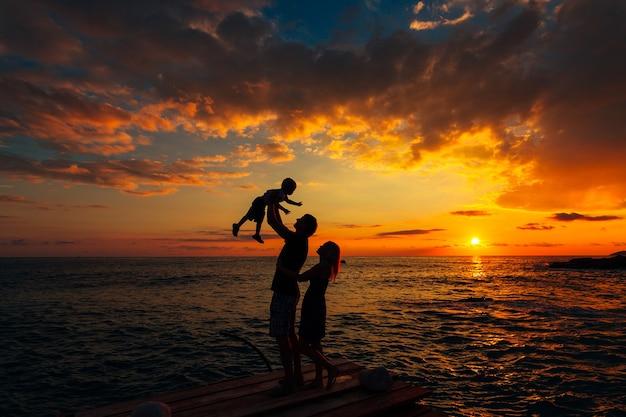 Silhouette der eltern mit einem kind auf see familie am strand i