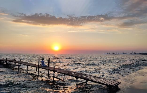Silhouette der frau, die bei sonnenuntergang auf dem schönen hölzernen angelpier auf dem meer sitzt
