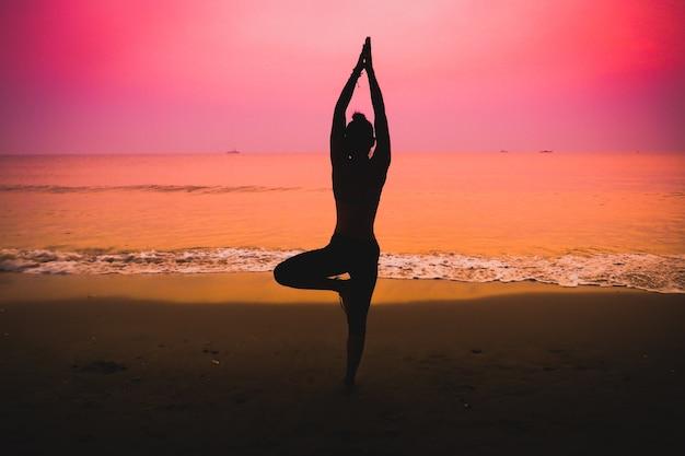 Silhouette der frau, die yoga auf einem strand
