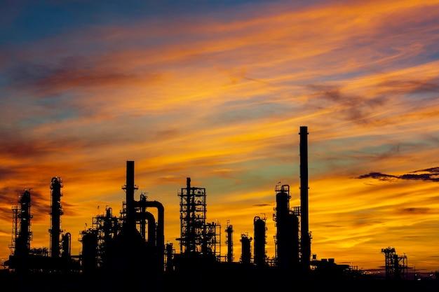 Silhouette der gasdestillation von tankölraffinerieanlagenturm und säulentanköl der petrochemie-industrie auf himmelssonnenuntergang-hintergrund