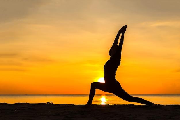 Silhouette der jungen frau, die bei sonnenuntergang yoga am strand praktiziert.