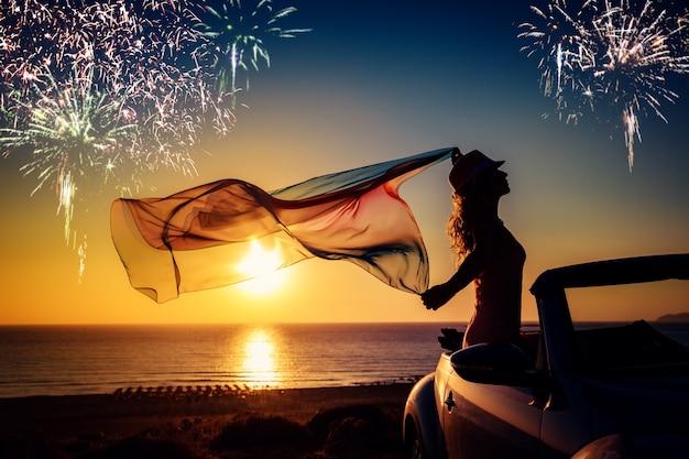 Silhouette der jungen frau, die sich am strandfeuerwerk im sonnenunterganghimmel-sommerferienkonzept entspannt