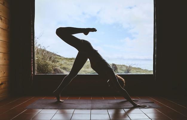 Silhouette der jungen frau, die yoga im innenbereich auf dem hintergrund des großen fensters mit natürlicher landschaft praktiziert