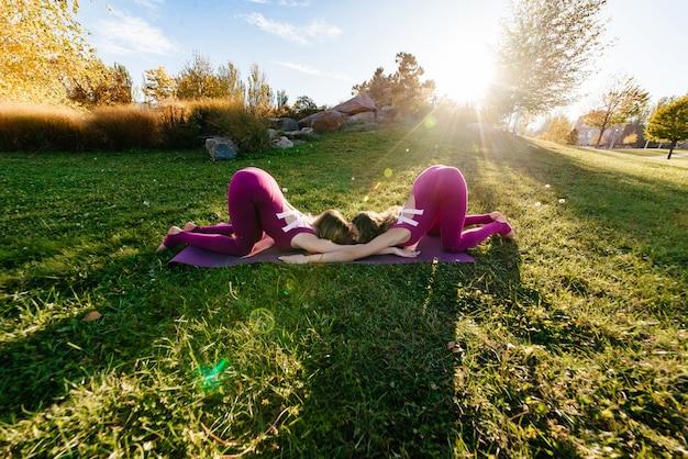 Silhouette der jungen frauen, die yoga oder pilates bei sonnenuntergang oder sonnenaufgang in der schönen berglage praktizieren