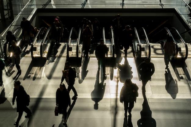 Silhouette der nicht erkennbaren passagier und touristen zu fuß auf die rolltreppe zum büro in der hauptverkehrszeit