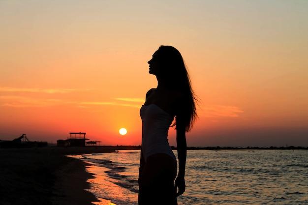 Silhouette der sexy frau in einem badeanzug an einem strand des ruhigen meeres während eines sonnenaufgangs