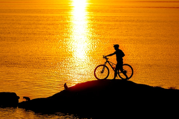 Silhouette der sportler mit dem fahrrad am strand