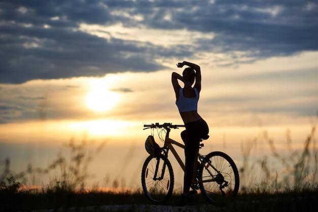 Silhouette der sportlichen radfahrerin