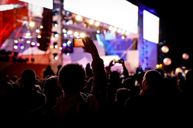 Silhouette der verwendung eines mobiltelefons bei einem konzert.