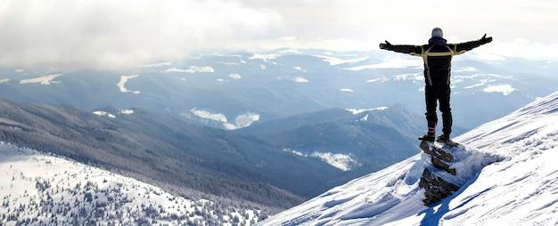 Silhouette des allein stehenden touristen, der auf schneebedeckter bergspitze in siegerhaltung mit erhabenen händen steht, die ansicht und leistung am hellen sonnigen wintertag genießen. abenteuer, aktivitäten im freien, gesunder lebensstil.
