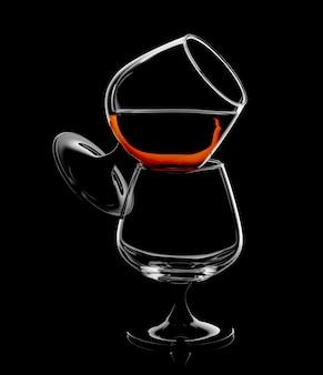 Silhouette des brandyschnüffelglases lokalisiert auf schwarzer oberfläche