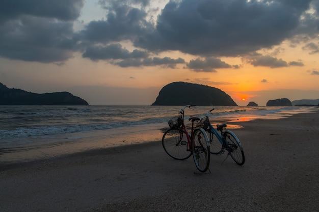 Silhouette des fahrrads am strand, fahrräder am strand sonnenuntergang oder sonnenaufgang