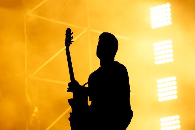 Silhouette des gitarristen, gitarrist auf konzertbühne durchführen. orange hintergrund, rauch, konzertscheinwerfer.