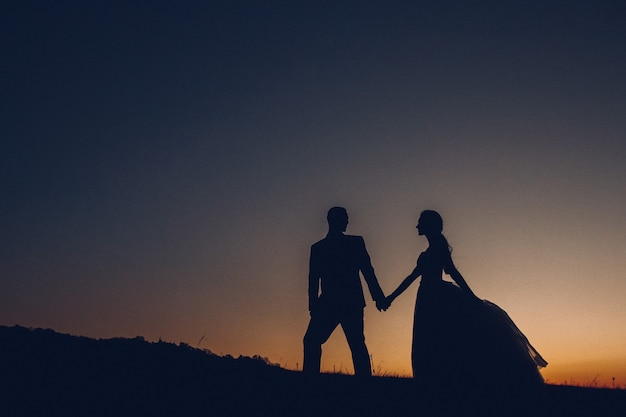Silhouette des hochzeitspaares, des bräutigams und der braut, die händchen halten auf dem hintergrund der sonne