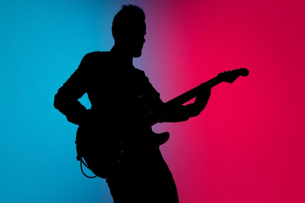 Silhouette des jungen kaukasischen männlichen gitarristen isoliert auf blau-rosa farbverlauf studio im neonlicht